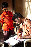 Govrind, a 12 year old boy deposits some of his money into the Savings Bank and Balgar, Madhiya Road, Kumbharwada.  The bank has been set up by the Balgar of the Shaishav Trust, Gujarati, India. The Shaishav Trust is trying to provide education and support for children in child labour.
