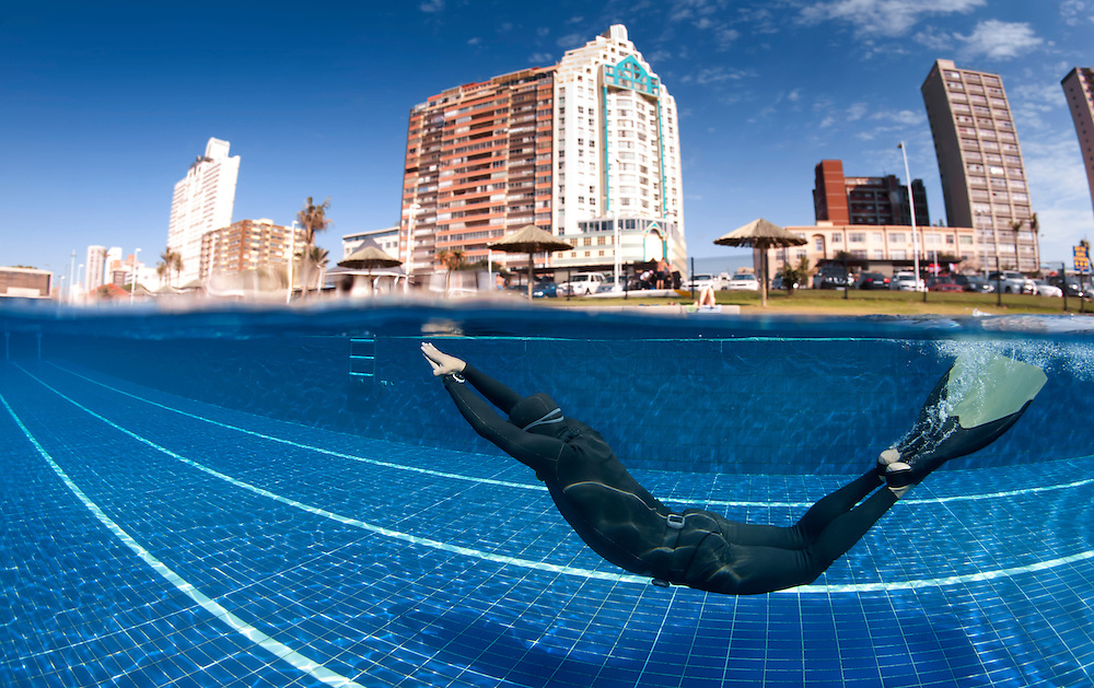 Spilt level underwater image of free diver Trevor Hutton free diving training in a swimming pool using a monofin with the Durban beachfront hotels in the background taken in Durban, KwaZulu Natal, South Africa