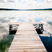 A wooden jetty extends out into a very calm Lake Peten Itza from Flores, Guatemala.