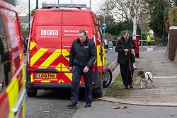 © Licensed to London News Pictures. 07/12/2019. London, UK. London Fire Brigade investigators with a sniffer dog gather evidence at the scene of a fatal road traffic collision after a black BMW hit a lamp post, the impact ripped the engine block from the car and it caught fire.<br /> Police were called at 09:08 GMT on Saturday 7th December 2019 to reports of a car in collision with a lamp post on Dollis Hill Lane at the junction with Brook Road, NW2. Metropolitan Police Officers, the London Ambulance Service and London Fire Brigade attended. Two people were recovered from the vehicle. The male driver was pronounced dead at the scene at 09:21 GMT. The passenger has been taken to a central London hospital. Photo credit: Peter Manning/LNP