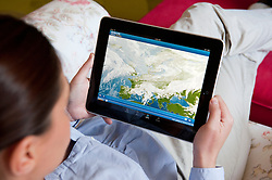 Woman using iPad tablet computer to check weather forecast in Europe