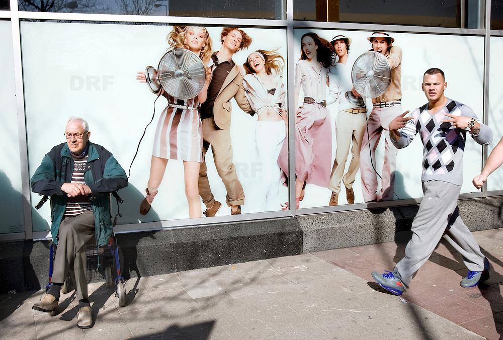 Nederland Rotterdam 21-03-2009 20090321Foto: David Rozing ..Oudere man zit op mobiel te wachten, naast hem een afbeelding met energieke jeugd  People Holland, The Netherlands, dutch, Pays Bas, Europe ..Foto: David Rozing