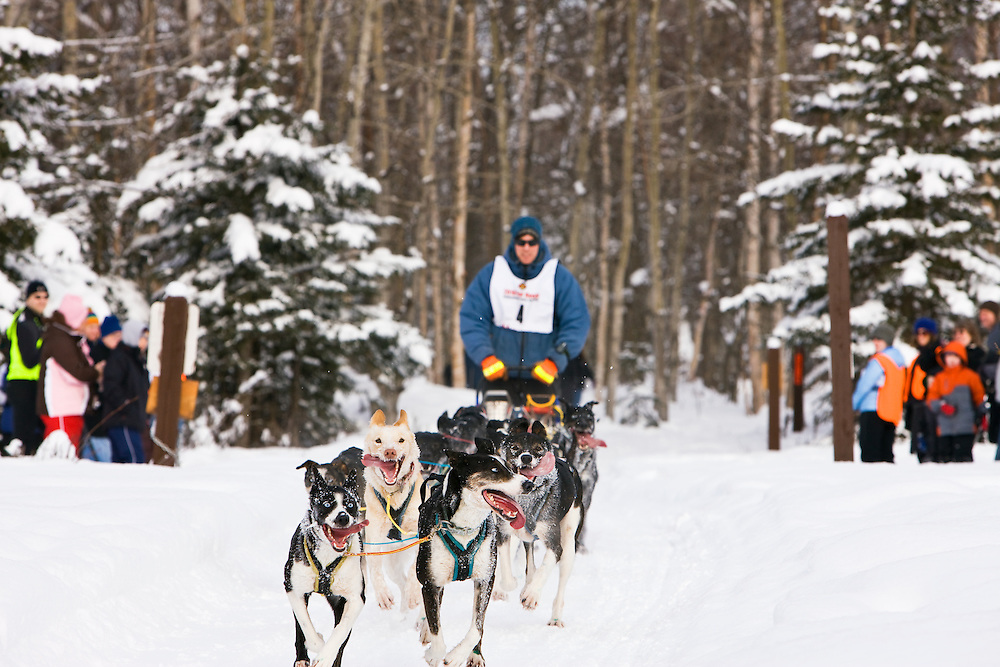 Musher Nils Hahn and sled dogs in the Fur Rendezvous World Sled Dog Championships on the Campbell Creek Trail in Anchorage, Alaska. Southcentral. Afternoon.