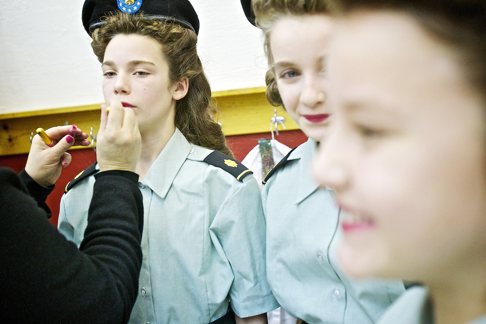 Isabelle McAfee, 10, left, has a fresh application of lip gloss before taking the stage as one of the Andrews Sisters alongside Sarena Kaschmitter, 11, center, and Carlee Piekarski, 10, at the Winton Elementary Pearl Harbor Day assembly Wednesday.