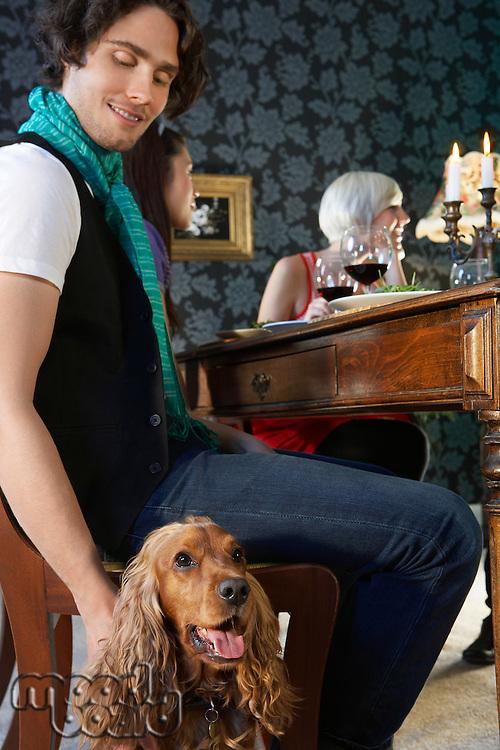Man petting dog sitting near dining table