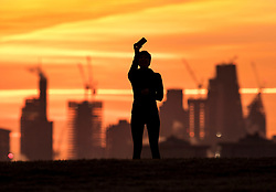 © Licensed to London News Pictures. 30/01/2018. London, UK. A jogger pauses at the top of a frosty Primrose Hill to take a phone photograph of the view as the sun rises over central London. Photo credit: Peter Macdiarmid/LNP