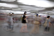 commuters and shoppers walking down a corridor at Yokohama train station