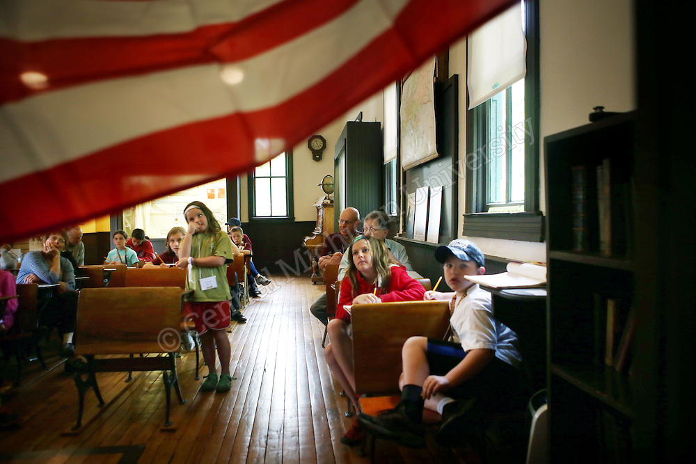 A girl asks a question about the American Flag in the One-Room Schoolhouse as part of Grandparents U photo Emily Mesner