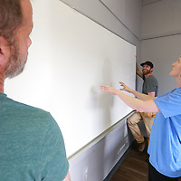 Brittany Cuevas lines up a whiteboard before volunteers finish hanging it in the new BLAST space for the Autism Center in Tupelo.
