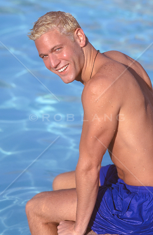 good looking all american man with blond hair and smiling while sitting by a swimming pool