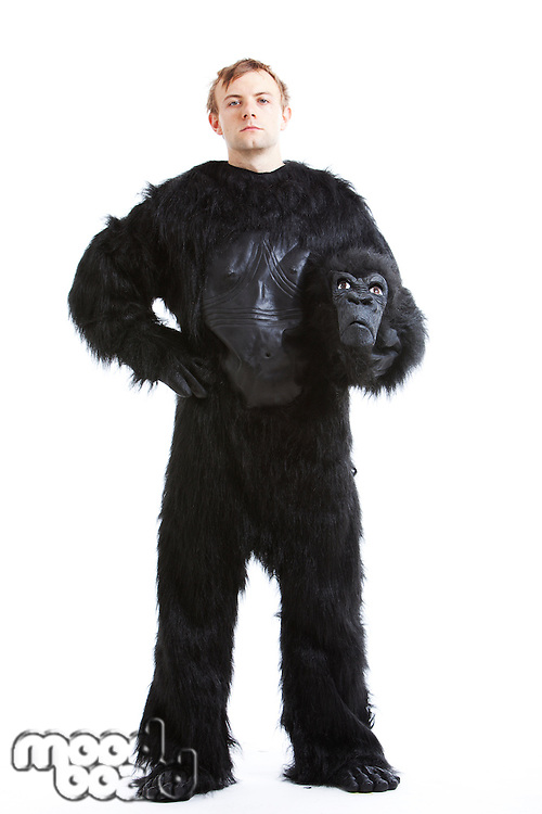 Portrait of young man in gorilla costume with hand on hip against white background