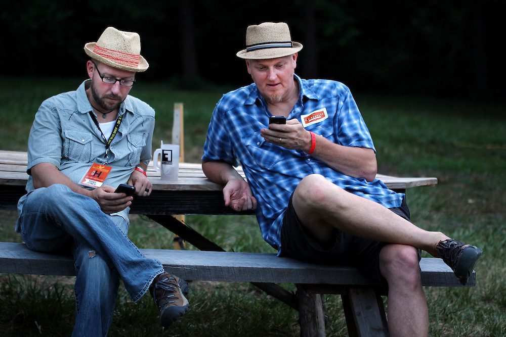 Authors Tony Jones, left, and Doug Pagitt, both of Minneapolis, read Tweets from the Wild Goose Festival at Shakori Hills in North Carolina June 24, 2011.  (Photo by Courtney Perry)