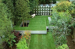 Overhead view showing three floating steel trays creating different levels of lawn. Betula utilis var. jacquemontii ( silver birch ) growing up through 'hole' in lawn. Workshop at rear of garden clad with aluminium disks. Design Diarmuid Gavin