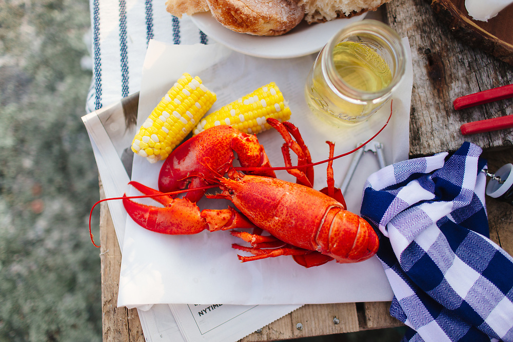 Lobsters and corncobs outdoors.