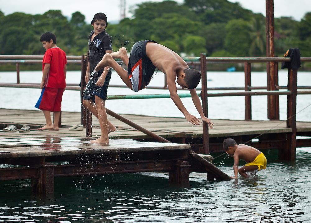 Children jump off a dock at Puerto Jiminez, Osa Peninsula, Costa Rica