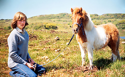 Family album picture of Lady Diana Spencer with Souffle, a Shetland pony, at her mother's home in Scotland during the summer of 1974.