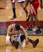 Blazers' Brandon Roy (7) is in pain on the court after a knee in the back of the head by the Rockets' Ron Artest... .