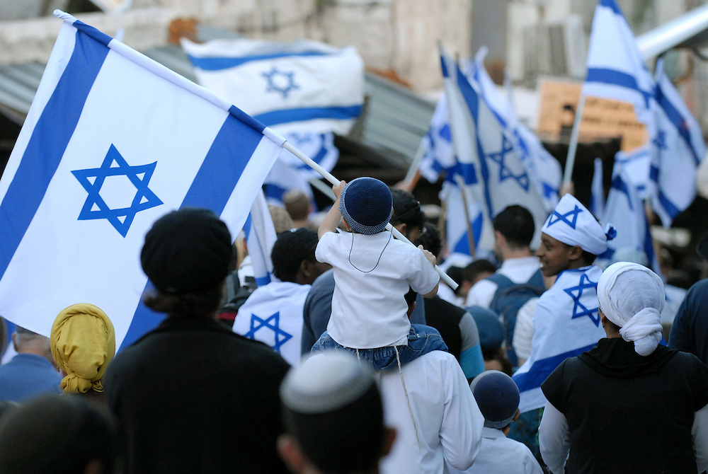 JERUSALEM, ISRAEL - MAY 12, 2010: An Israeli child waves an Israeli flag in the Muslim Quarter of Jerusalem's Old city during a march celebrating Jerusalem Day, Thursday, May 12, 2010. Thousands took part in Jerusalem Day celebrations in the capital, marked the 43nd anniversary of its capture of Arab east Jerusalem in the Six Day War of 1967. Photo by GILI YAARI/NEWS-PICTURES