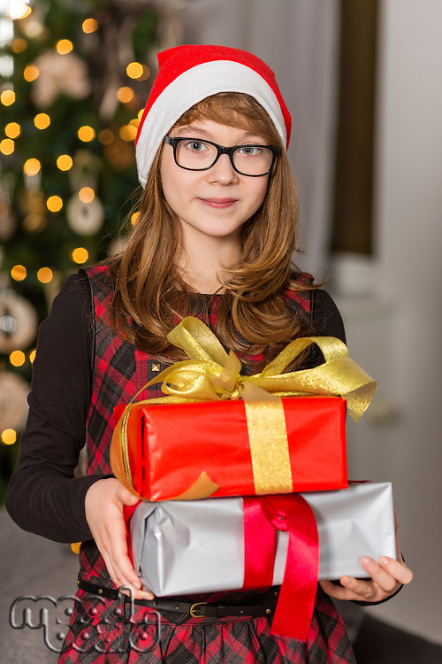 Portrait of teenage girl holding stack of Christmas presents