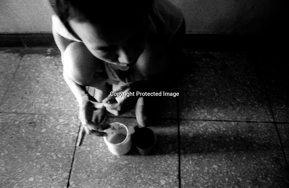 """BEIJING/7/23/2002:Wang Lanrong,53,spends the afternoon by herself in the corridor of a mental hospital in Beijing.She has lived in mental institutions for the past thirty years.She¥s schizophrenic and her disease was triggered during  the cultural revolution when Wang was  a young girl (1966-76).. In her """"own world"""" Wang thinks of herself as a man.   .Wang 's conditioned worsened in early 2003 and she passed away in September.. ."""