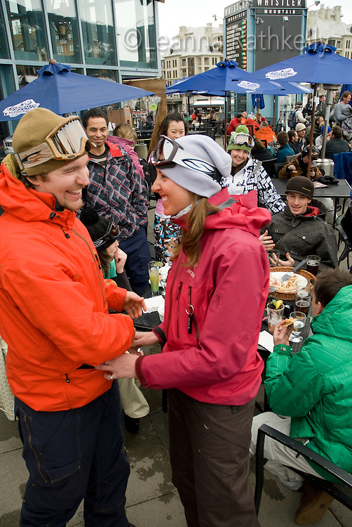 Group enjoys an apres-ski snack and drink on the outdoor deck of the Garibaldi Lift Company bar in Whistler, BC