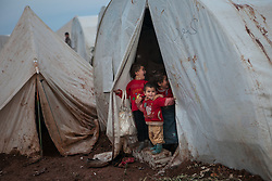 Children gather in front of their tent looking at the photographer's camera inside Atmah's refugee camp Idlib province, Syria. Situated along the Turkish border Atmah's refugee camp is considered the biggest refugee camp inside Syria's territory with an estimated number of 13,000 refugees and growing by the day. Is the biggest in an area with another two camps.,000 refugees and growing by the day. Is the biggest in an area with another two camps, Syria, February 5, 2013. Photo by Daniel Leal-Olivas / i-Images.