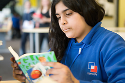 Secondary School student reading a book in the library at lunch break,