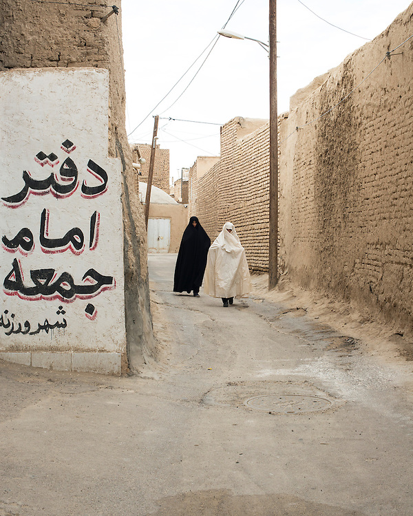 Women wearing black and white chador walking in a lane