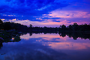 """01 JULY 2013 - ANGKOR WAT, SIEM REAP, SIEM REAP, CAMBODIA:  The moat the surrounds Angkor Wat at sunset. Angkor Wat is the largest temple complex in the world. The temple was built by the Khmer King Suryavarman II in the early 12th century in Yasodharapura (present-day Angkor), the capital of the Khmer Empire, as his state temple and eventual mausoleum. Angkor Wat was dedicated to Vishnu. It is the best-preserved temple at the site, and has remained a religious centre since its foundation– first Hindu, then Buddhist. The temple is at the top of the high classical style of Khmer architecture. It is a symbol of Cambodia, appearing on the national flag, and it is the country's prime attraction for visitors. The temple is admired for the architecture, the extensive bas-reliefs, and for the numerous devatas adorning its walls. The modern name, Angkor Wat, means """"Temple City"""" or """"City of Temples"""" in Khmer; Angkor, meaning """"city"""" or """"capital city"""", is a vernacular form of the word nokor, which comes from the Sanskrit word nagara. Wat is the Khmer word for """"temple grounds"""", derived from the Pali word """"vatta."""" Prior to this time the temple was known as Preah Pisnulok, after the posthumous title of its founder. It is also the name of complex of temples, which includes Bayon and Preah Khan, in the vicinity. It is by far the most visited tourist attraction in Cambodia. More than half of all tourists to Cambodia visit Angkor.      PHOTO BY JACK KURTZ"""