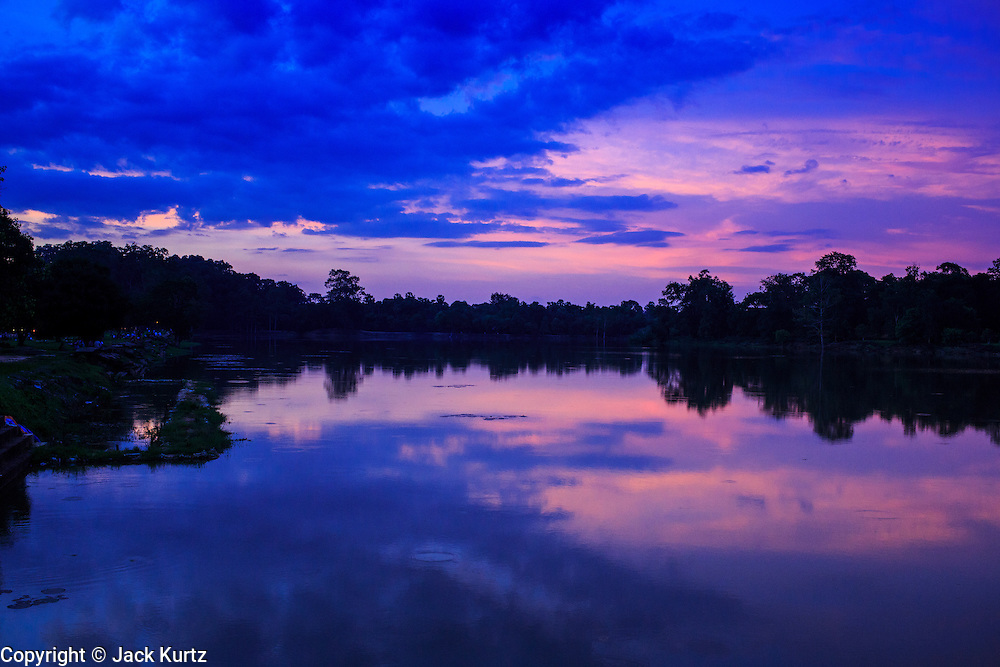 "01 JULY 2013 - ANGKOR WAT, SIEM REAP, SIEM REAP, CAMBODIA:  The moat the surrounds Angkor Wat at sunset. Angkor Wat is the largest temple complex in the world. The temple was built by the Khmer King Suryavarman II in the early 12th century in Yasodharapura (present-day Angkor), the capital of the Khmer Empire, as his state temple and eventual mausoleum. Angkor Wat was dedicated to Vishnu. It is the best-preserved temple at the site, and has remained a religious centre since its foundation – first Hindu, then Buddhist. The temple is at the top of the high classical style of Khmer architecture. It is a symbol of Cambodia, appearing on the national flag, and it is the country's prime attraction for visitors. The temple is admired for the architecture, the extensive bas-reliefs, and for the numerous devatas adorning its walls. The modern name, Angkor Wat, means ""Temple City"" or ""City of Temples"" in Khmer; Angkor, meaning ""city"" or ""capital city"", is a vernacular form of the word nokor, which comes from the Sanskrit word nagara. Wat is the Khmer word for ""temple grounds"", derived from the Pali word ""vatta."" Prior to this time the temple was known as Preah Pisnulok, after the posthumous title of its founder. It is also the name of complex of temples, which includes Bayon and Preah Khan, in the vicinity. It is by far the most visited tourist attraction in Cambodia. More than half of all tourists to Cambodia visit Angkor.      PHOTO BY JACK KURTZ"
