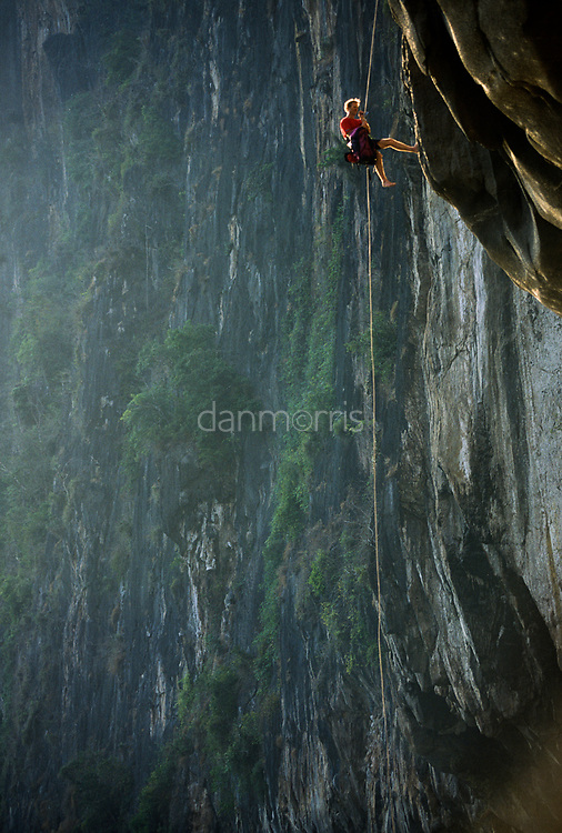 Will Hair abseils down high above Nam Ou River, Ban Pak Ou, Luang Phrabang, Laos