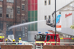 © Licensed to London News Pictures . 14/07/2013 . Manchester , UK . Firecrews at the scene where a fire fighter, identified as Stephen Hunt, died while tackling a fire in a store-room of Paul's Hair World in Oldham Street, Manchester. Two 15-year-old girls arrested on suspicion of manslaughter. Photo credit : Joel Goodman/LNP