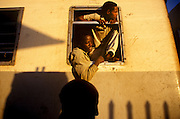 Men hanging out of the window on the train between Djibouti and Addis Ababa.