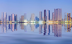 Night skyline view of modern high-rise apartment buildings along Corniche in Sharjah United Arab Emirates