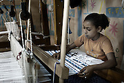 "A girl learns to weave carpets   in the workshop of the NGO, APE in Mokattam, using recycled scraps of clothing and textiles from factories throughout Egypt.On the outskirts of Cairo in the middle of Manshiet Nasr neighborhood is located Mokattam settlement known as ""Garbage City"" is inhabited by Zabbaleen, a community of about 45,000 Coptic Christians living for decades to recycle waste generated by the Egyptian capital: plastic, aluminum, paper and organic waste transformed into compost. Most part of the Association for the Protection of the Environment (APE), an NGO that works in the area, whose objectives are to protect the environment and improve the livelihoods of garbage scavengers in Cairo. According to the UN, the work is done in Mokattam is one of the ten best examples of world environmental improvement. El Cairo , Egipt, June 2011. ( Photo by  Jordi Camí )."