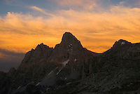 Fiery clouds glow at sunset behind the high peaks of the Tetons in Grand Teton National Park, Jackson Hole, Wyoming.