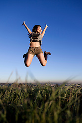 Smiling Young Woman Jumping Mid Air Outdoors