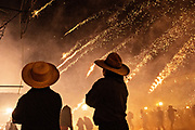 Two cowboys watch as sky rockets rain down on celebrants in the chaos of the Alborada festival in front of the Parroquia San Miguel Archangel church September 29, 2018 in San Miguel de Allende, Mexico. The unusual festival celebrates the cities patron saint with a two hour-long firework battle at 4am representing the struggle between Saint Michael and Lucifer.