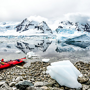 A bright red tandem kayak is pulled up on the rocky shore of Cuverville Island, Antarctica, with glassy waters in the background covered with icebergs and brash ice.