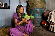 Sadma Khan, 19, plays with Lucky, a pet parakeet, in her mother's one-room house which she shares with 5 other family members in a slum area of Tonk, Rajasthan, India, on 19th June 2012. She was married at 17 years old to Waseem Khan, also underaged at the time of their wedding. The couple have an 18 month old baby and Sadma is now 3 months pregnant with her 2nd child and plans to use contraceptives after this pregnancy. She lives with her mother since Waseem works in another district and she can't take care of her children on her own. Photo by Suzanne Lee for Save The Children UK