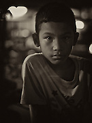 Boy in the streets of Pattaya who is selling food with his mother