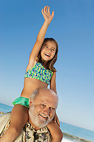 Girl sitting on grandfather's shoulders on beach arm raised
