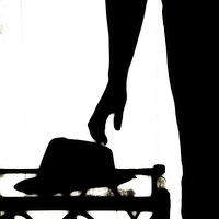 Silhouette of a person about to pick up a trilby hat