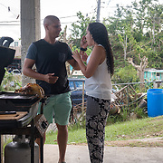 NOVEMBER 23 - TOA ALTA, PUERTO RICO - <br /> Angel Joel Alvarez, 34, gives girlfriend Michelle Vazquez Ojeda, 21, a taste of the turkey cooked by him using a gas BBQ grill in his mother in law's garage in the Comunidad Las Acerolas. The house has been without power since Hurricane Maria and it's sheltering several family members.<br /> (Photo by Angel Valentin/FREELANCE)