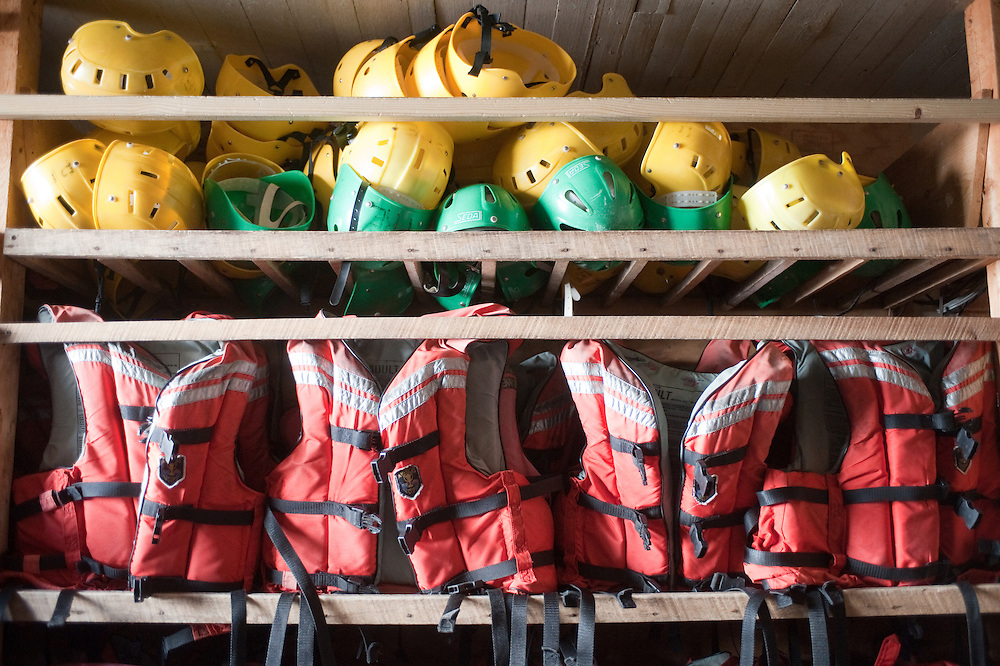 Whitewater helmets and lifevests on the rack