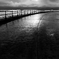 Iron Railings on the Sea Wall and Reflections after Rain in Souith Bay Scarborough North Yorkshire England