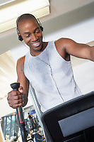 Sweaty man on elliptical machine in health club listening to headphones