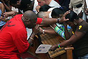 Woman being blessed by Rev. Stephen W. Pogue, the Pastor, while other devotees are praying in silence in front of the altar, during a Mass Service at the Hip Hop Church in Harlem, New York, NY., on Thursday, July 21, 2006. A new growing phenomenon in the United States, and in particular in its most multiethnic city, New York, the Hip Hop Church is the meeting point between Hip Hop and Christianity, a place where ëGodí is worshipped not according to religious dogmatisms and rules, but where the ëHoly Spirití is celebrated by the community through young, unique, passionate Hip Hop lyrics. Its mission is to present the Christian Gospel in a setting that appeals to both, those individuals who are confessed Christians, as well as those who are not regularly attending traditional Services, while helping many youngsters from underprivileged neighbourhoods to feel part of a community, to make them feel loved and to help them not to give up when problems arise. The Hip Hop Church is not only forward-thinking but it also has an important impact where life at times can be difficult and deceiving, and where young people can be easily influenced for the worst purposes. At the Hip Hop Church, members are encouraged to sing, dance and express themselves in any way that the ëSpirit of Godí moves them. Honours to students who have overcome adversity, community leaders, church leaders and some of the unsung pioneers of Hip Hop are common at this Church. Here, Hip Hop is the culture, while Jesus is the centre. Services are being mainly in Harlem, where many African Americans live; although the Hip Hop Church is not exclusive and people from any ethnic group are happily accepted and involved with as much enthusiasm. Rev. Ferguson, one of its pioneer founders, has developed ëHip-Hop Homileticsí, a preaching and worship technique designed to reach the children in their language and highlight their sensibilities, while bringing forth Christianity. This ëKeep It Realí evangelism style is t