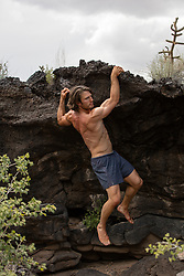 man in shorts climbing on volcanic rocks