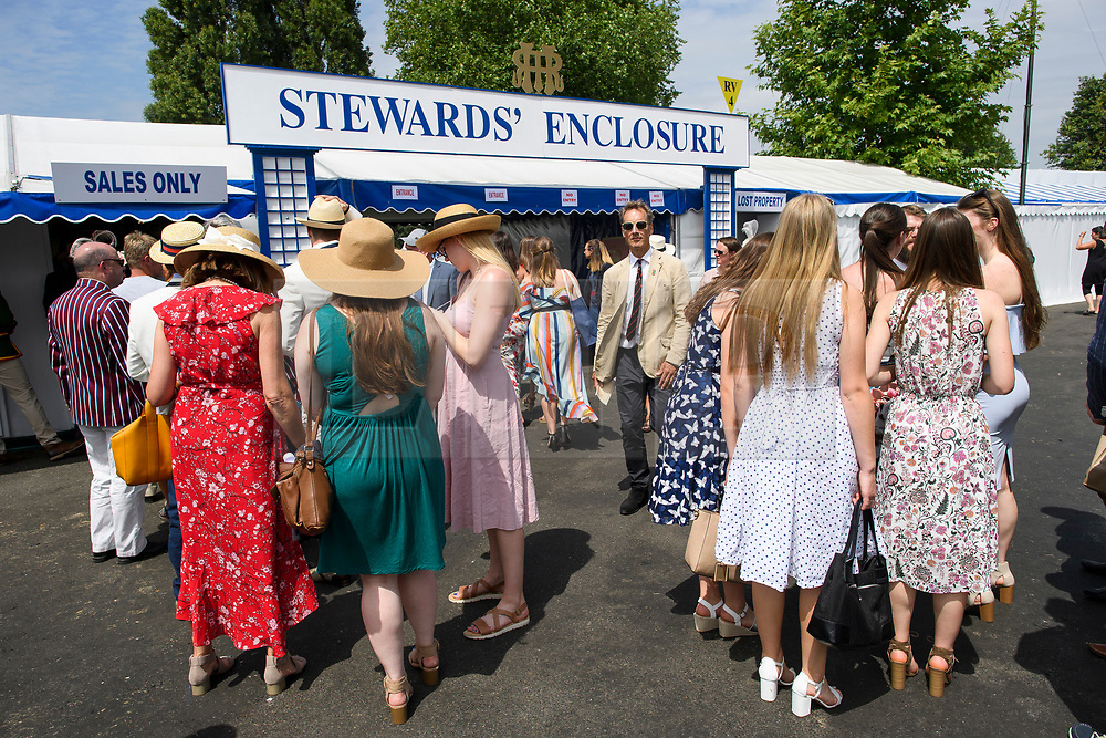 © Licensed to London News Pictures. 04/07/2018. Henley-on-Thames, UK. Women in dress gather outside the Steward's Enclosure as day one of the Henley Royal Regatta, set on the River Thames by the town of Henley-on-Thames in England. Established in 1839, the five day international rowing event, raced over a course of 2,112 meters (1 mile 550 yards), is considered an important part of the English social season. Photo credit: Ben Cawthra/LNP